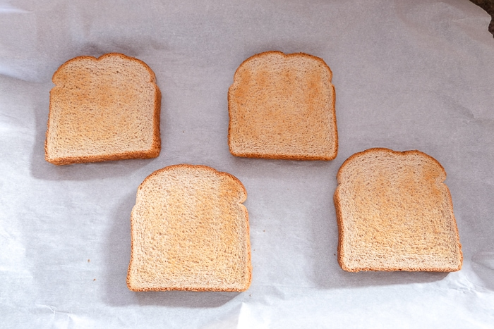 four piece of bread on parchment paper on baking sheet