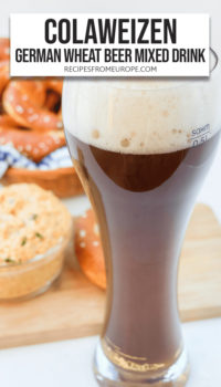 """Dark beverage in wheat beer glass with cheese spread and pretzels in the background plus text overlay saying """"Colaweizen German Wheat Beer Mixed Drink"""""""