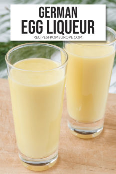 Two glasses with yellow egg liqueur on wooden board with green tree branch in background and text overlay for Pinterest