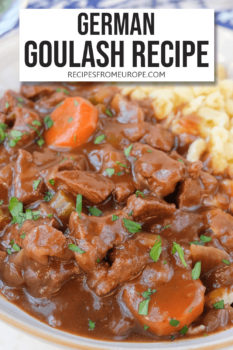 """Beef chunks and carrot slices in brown sauce in bowl with parsley sprinkled on top and spaetzle noodles in the background plus text overlay saying """"German goulash recipe"""""""