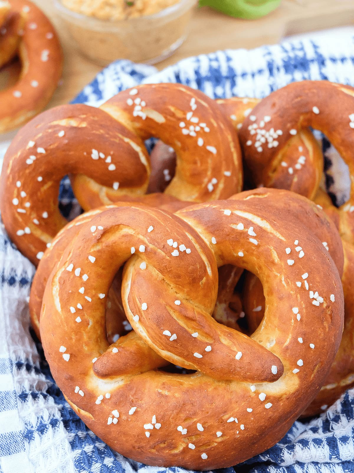German pretzels with coarse salt on top in basket with blue and white dish towel