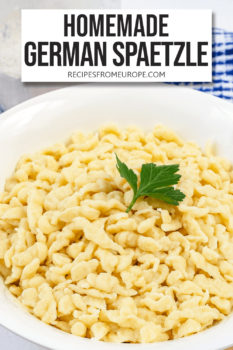 Photo of spaetzle noodles in white bowl with parsley for decoration and text overlay for Pinterest