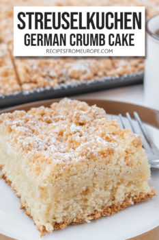"""Slice of streusel cake on white plate with brown rim and fork next to it with text overlay saying """"Streuselkuchen German crumb cake"""""""