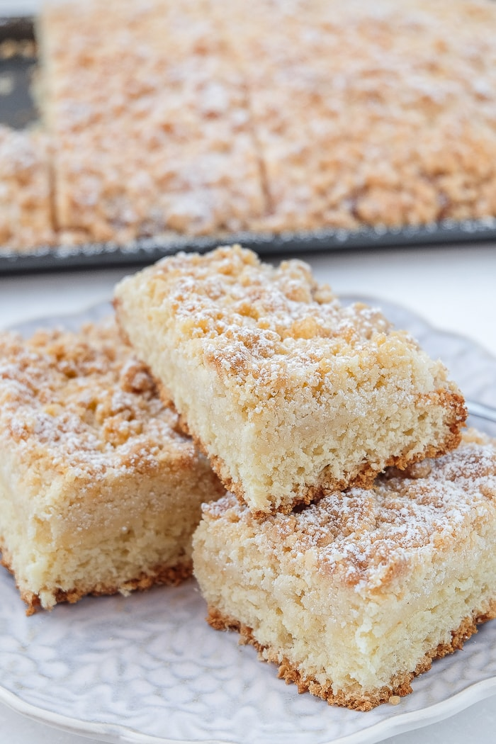 german streuselkuchen slices stacked on plate with crumb cake behind
