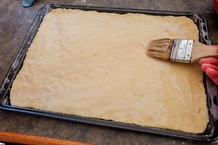 Streuselkuchen dough brushed with milk on counter with paint brush beside