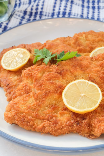 breaded german schnitzel on plate with slices of lemon