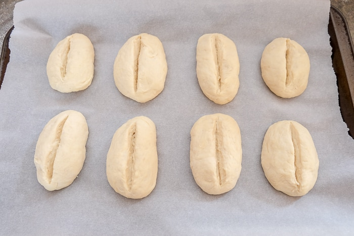 bread rolls with slits cut on top on parchment paper pan