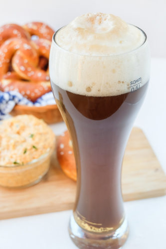 german colaweizen drink in tall beer glass with pretzels behind