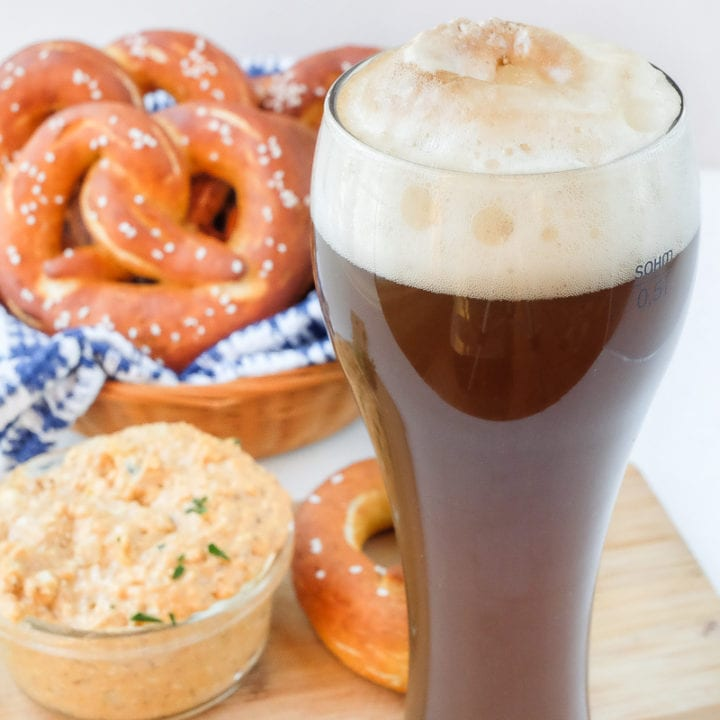 german colaweizen drink in tall glass with pretzels and cheese behind