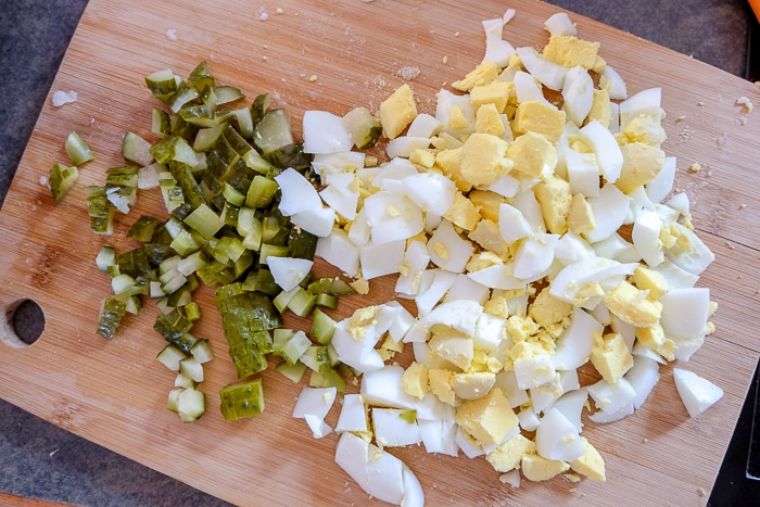 eggs and pickles chopped small on wooden cutting board