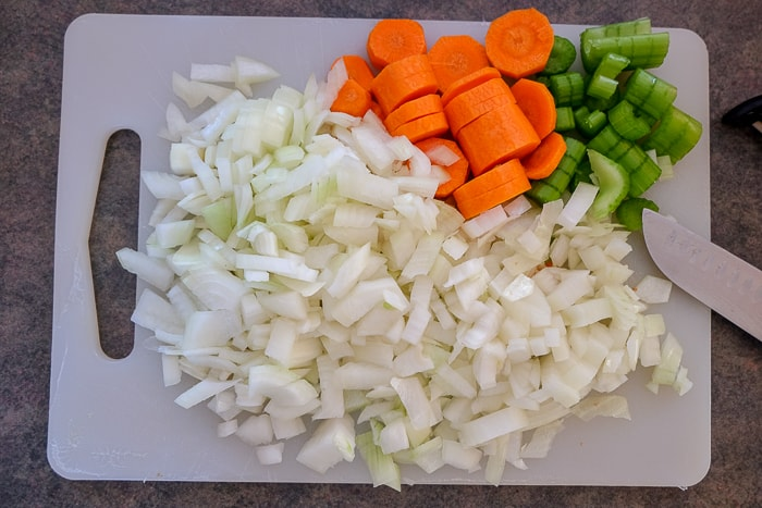 chopped carrots onions and celery on white cutting board