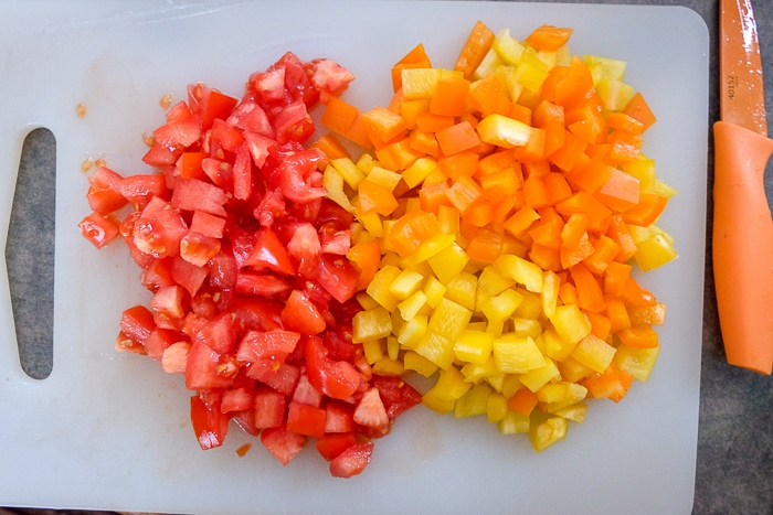 chopped red and orange peppers on white cutting board