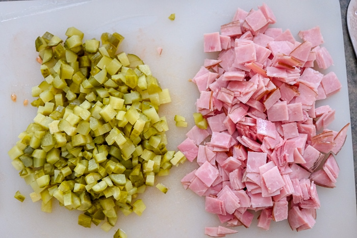 chopped pickles and ham on white cutting board