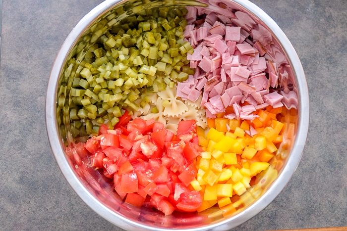 chopped vegetables and pasta in metal bowl for pasta salad