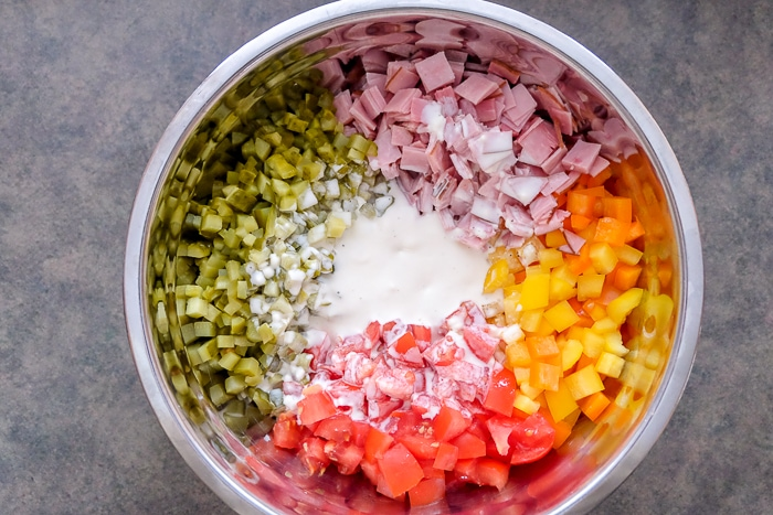 pasta salad ingredients in bowl ready to be mixed