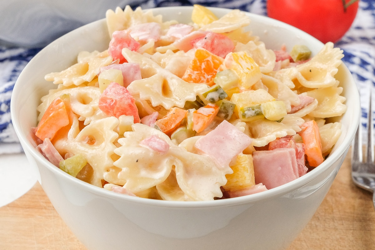 german pasta salad with bowties and peppers in white bowl on wood