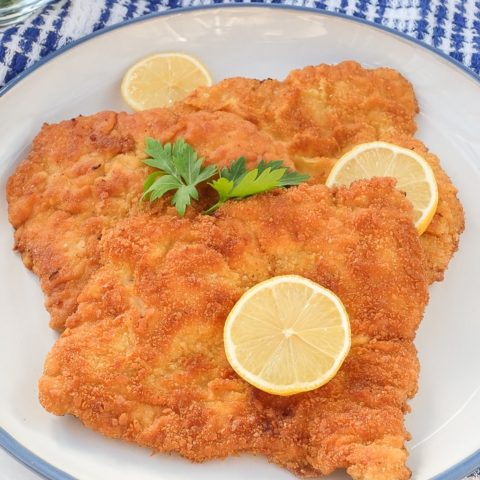 pieces of german schnitzel with slices of lemon on plate