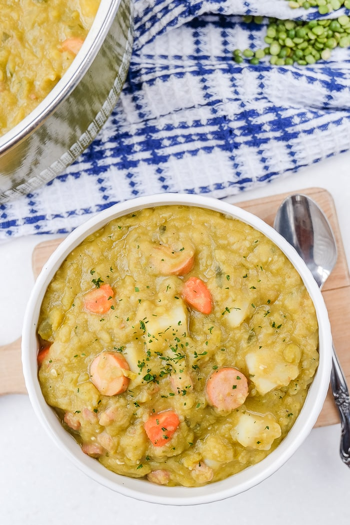bowl of german split pea soup with blue towel and spoon beside