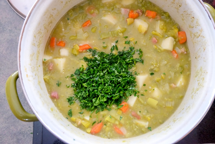 chopped parsley on simmering split pea soup in pot on stove