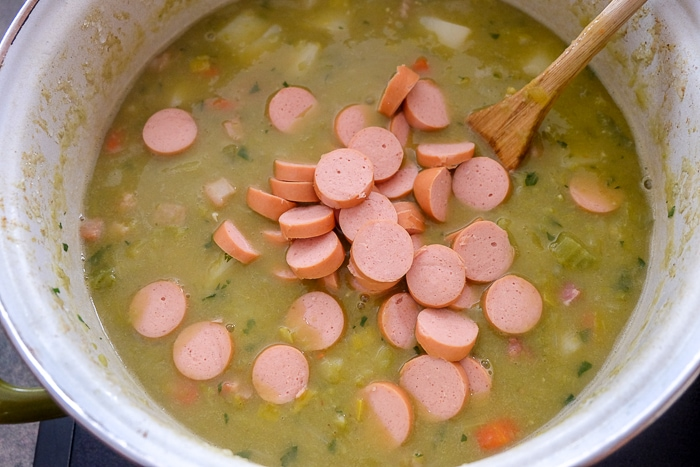 chopped weiner sausage in split pea soup in pot on stove with wooden spoon