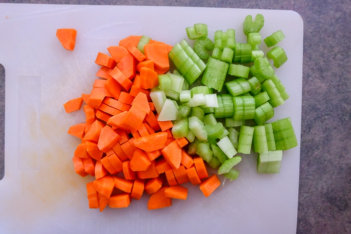 chopped celery and carrots on white cutting board