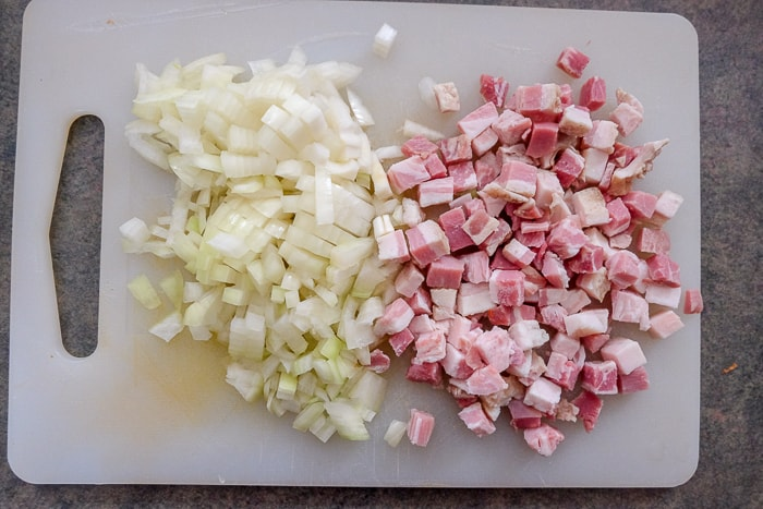 chopped onions and pancetta bacon on white cutting board