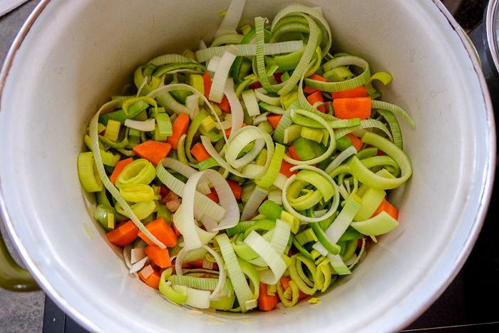 chopped raw vegetables in large soup pot on stove