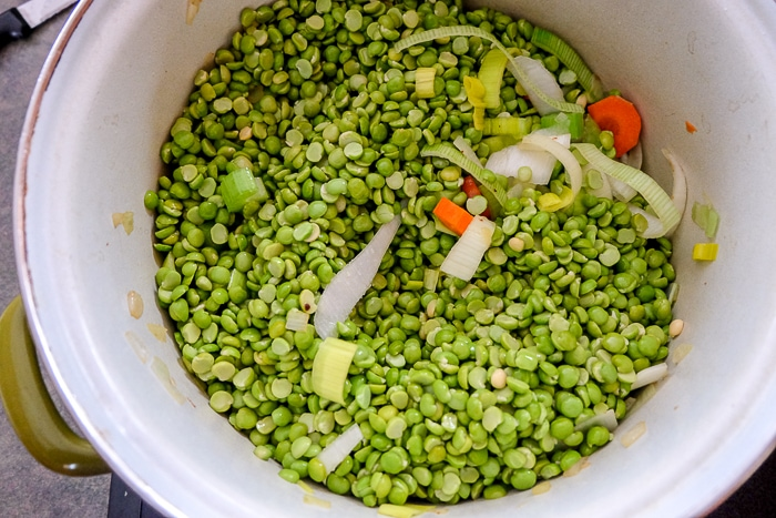 split peas on vegetables in soup pot on stove