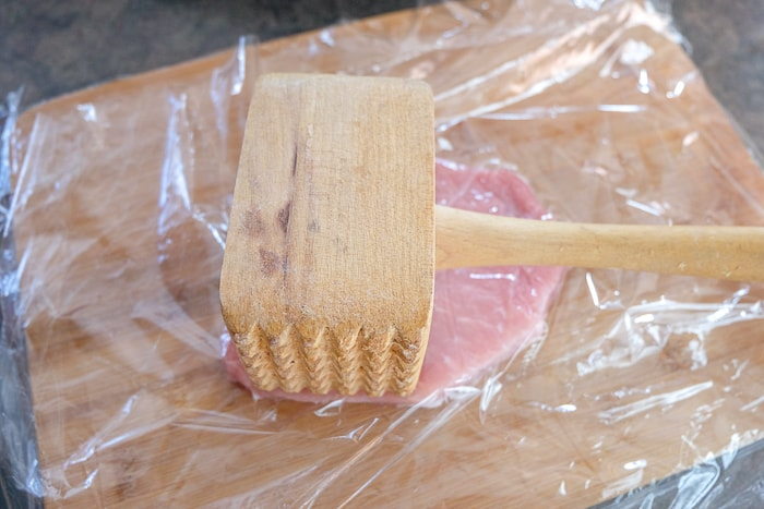 wooden meat hammer laying on pork chop under plastic wrap