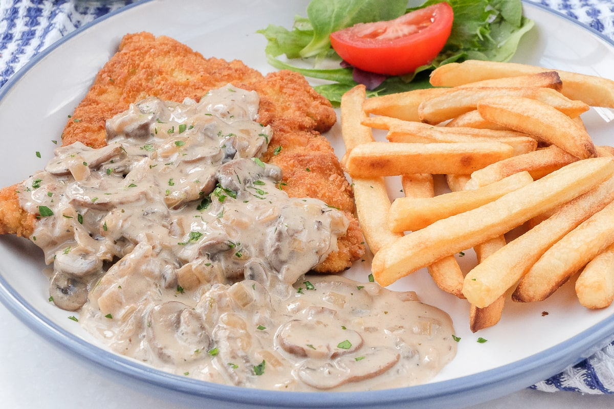 Jägerschnitzel on plate with fries and small salad behind