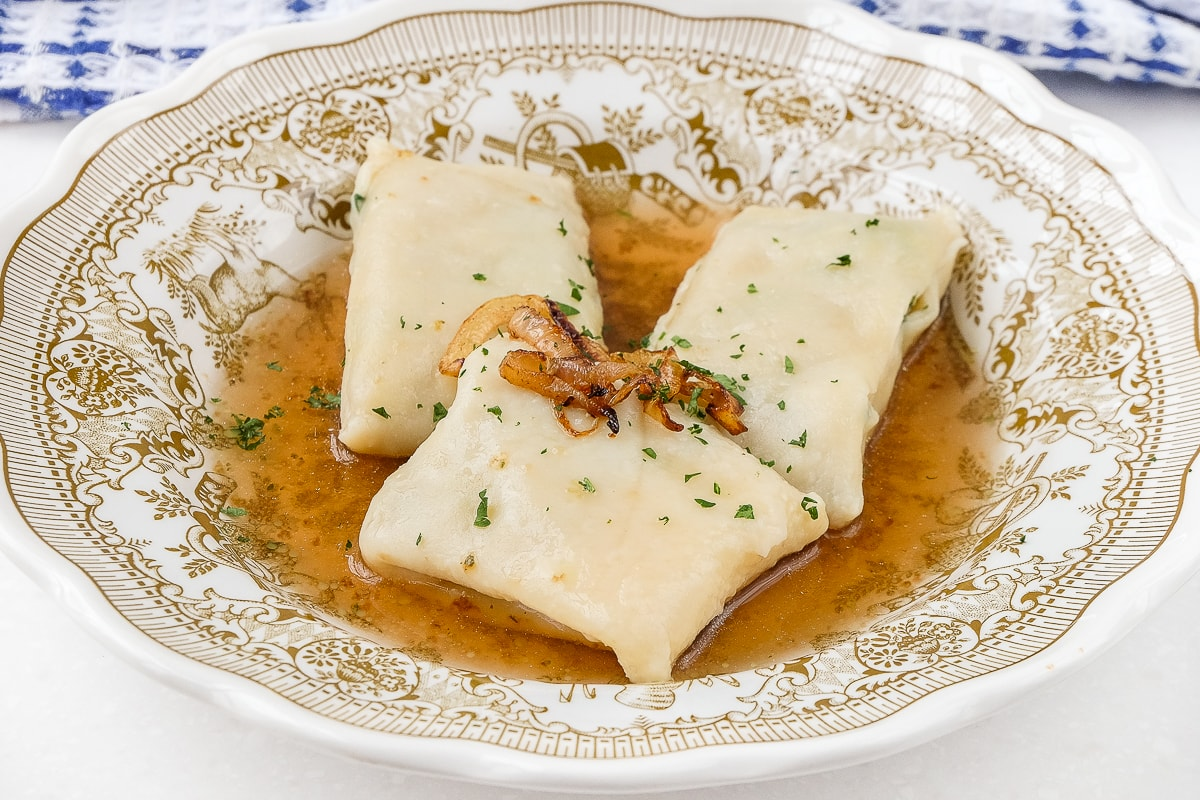 bowl of maultaschen meat pasta with broth and onions