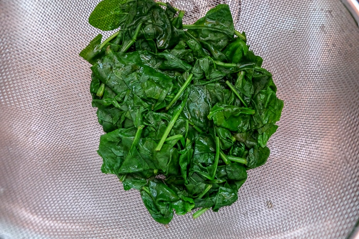 cooked spinach in strainer in sink