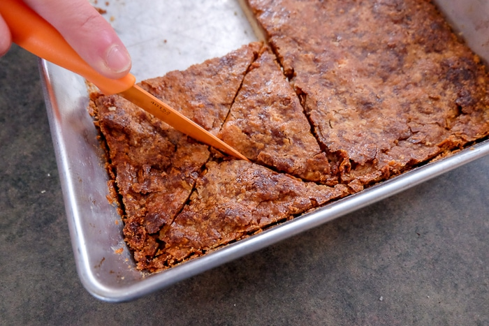 cutting nussecken bars into triangles with knife in pan