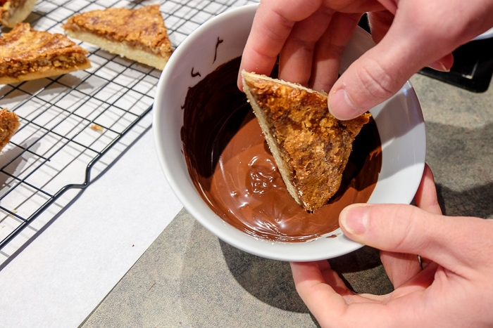 nussecken bar in hand dipping in bowl of melted chocolate
