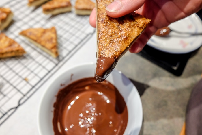 nussecken with corner dipped in chocolate with cooling rack behind