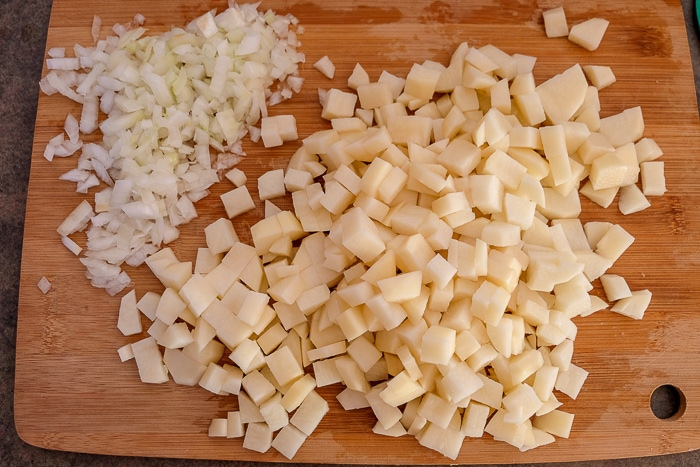 potatoes and onions chopped on wooden cutting board