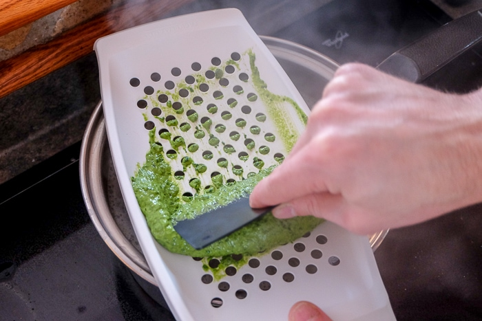 hand scraping green spinach spaetzle batter on white spaetzle grater