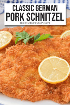 """Slices of breaded and fried schnitzel on plate with slice of lemon on top plus text overlay saying """"classic German pork schnitzel"""""""