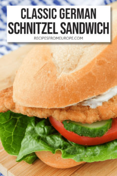 """Crusty roll with lettuce tomato cucumber breaded schnitzel and mayonnaise on cutting board and text overlay saying """"classic German schnitzel sandwich"""""""