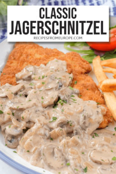 """Breaded schnitzel with brown mushroom gravy on plate with blue rim and text overlay saying """"classic jagerschnitzel"""""""