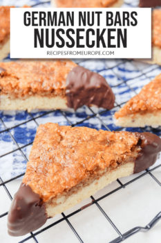 """Nut bars cut into triangles with chocolate dipped corners on black cooling tray with text overlay saying """"German nut bars Nussecken"""""""
