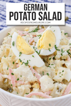 """Potato salad in white bowl with sliced egg and chopped parsley on top plus text overlay saying """"german potato salad"""""""