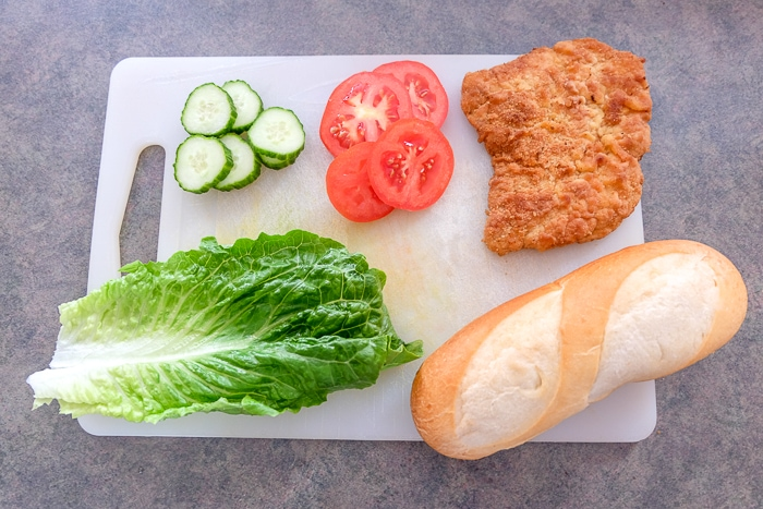 cutting board on counter with bun and vegetables and schnitzel on top