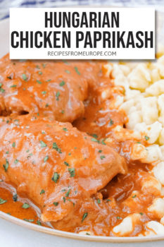 """chicken thigh with red sauce on plate with yellow egg noodles and text overlay saying """"Hungarian chicken paprikash"""""""