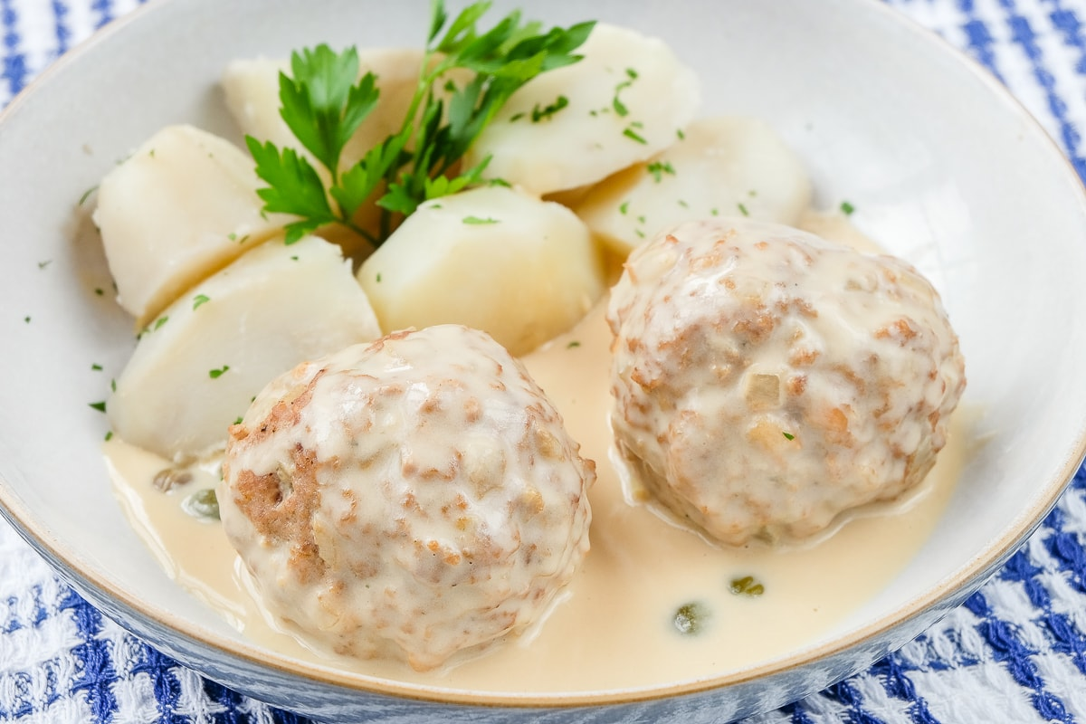two Konigsberger Klopse in a dish with potatoes and parsley