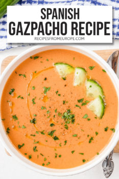 """orange cold soup in white bowl with chopped cucumber and chopped parsley on top plus text overlay saying """"Spanish gazpacho recipe"""""""