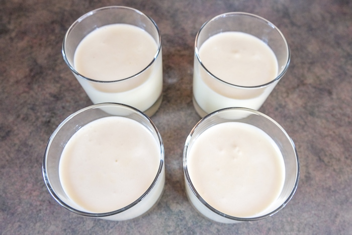 pouring bavarian cream into four glasses on counter