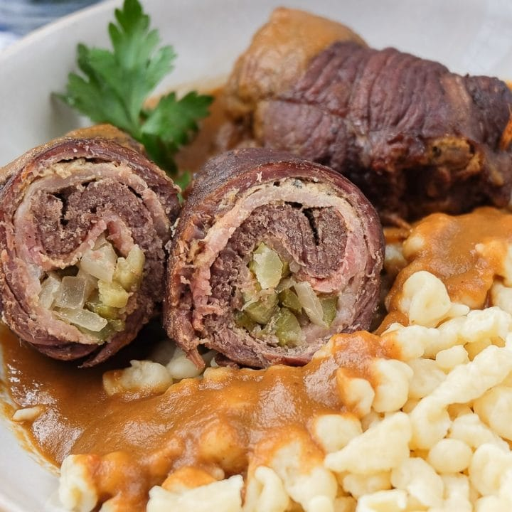 two german rouladen in bowl with spaetzle and gravy