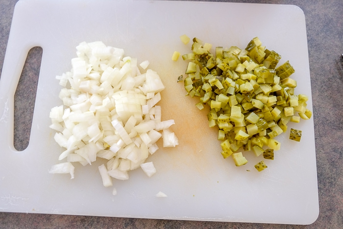 chopped onions and pickles on white cutting board for rouladen
