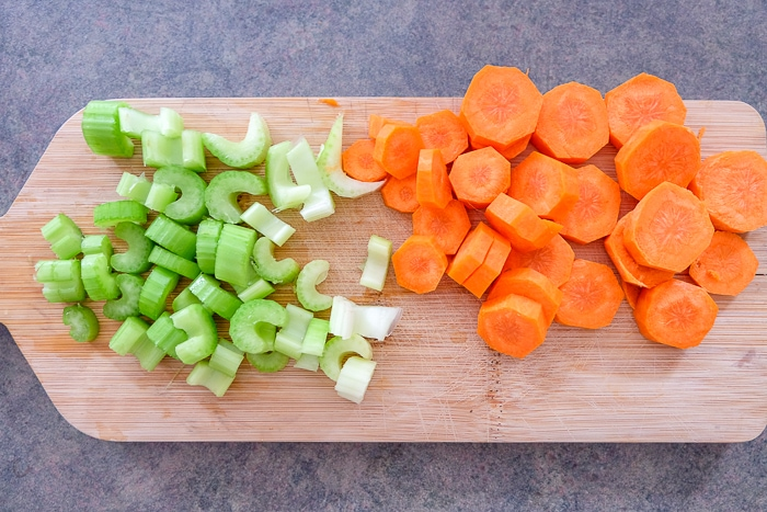 sliced carrots and celery on wooden cutting board on counter